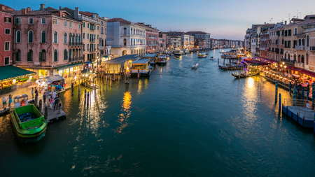 Grand Canal in Venice, Italy day to night transition timelapse. View on gondolas and city lights from Rialto Bridge. Beautiful and romantic Italian city on water.