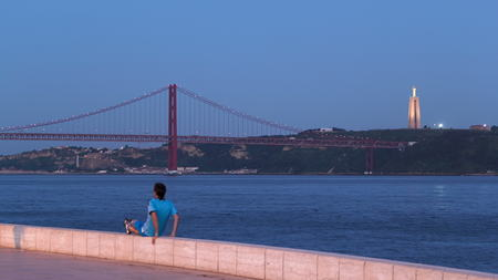 Bridge 25 de Abril on river Tagus at twilight with Cristo, view from Belem Tower, Lisbon, Portugal timelapse 4K Stock Photo