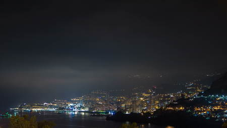 Cityscape of Monte Carlo at night timelapse, Monaco. Evening mist become to clouds. Night illumination of buildings. Yachts in harbor. Top view from Cap Martin