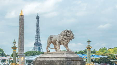 One of the two marble lions of the Tuileries garden overhanging the Concorde place in Paris timelapse, with its obelisk of Luxor and its rostral columns, and the Eiffel Tower in the background Stock Photo