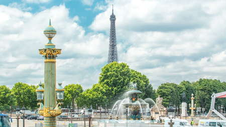 Fontaines de la Concorde on Place de la Concorde timelapse in Paris, France. Traffic on road and eiffel tower on background. Blue cloudy sky at summer day