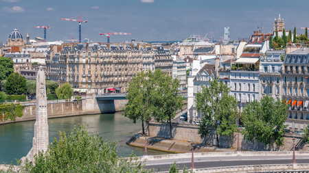 Panorama of Paris timelapse with Cite Island. View from observation deck of Arab World Institute (Institut du Monde Arabe) building. Top aerial view. Green trees, Seine river, Blue cloudy sky at summer day. France.
