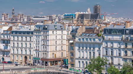 Panorama of Paris timelapse with houses and traffic on road. View from observation deck of Arab World Institute (Institut du Monde Arabe) building. Top aerial view. Green trees, Seine river, Blue cloudy sky at summer day. France.