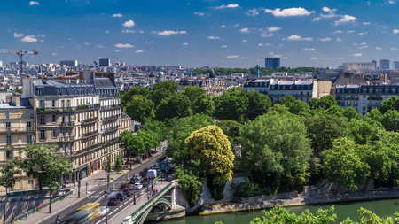 Panorama of Paris timelapse with Bastille column and traffic on road. View from observation deck of Arab World Institute (Institut du Monde Arabe) building. Top aerial view. Green trees, Seine river, Blue cloudy sky at summer day. France.