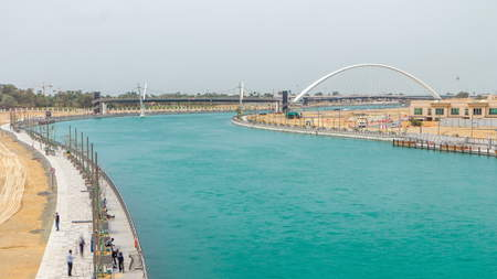 Two bridges over newly opened Dubai canal with a boat crossing under them timelapse. Voew from bridge with cloudy sky at day time