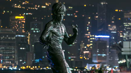 Bruce Lee monument timelapse hyperlapse in the night at the Avenue of stars, modern skyscrapers at the background in Hong Kong. Bruce Lee was  the most influential and famous  martial artist of the 20th century. 4K Editorial