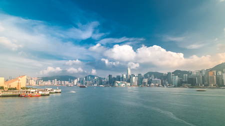 Hong Kong Harbor panorama cityscape timelapse with blue cloudy sky - Central District, Victoria Harbor, Victoria Peak, Hong Kong Island and Kowloon, Hong Kong. Wide angle view. 4K