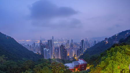 The famous view of Hong Kong from night to day transition timelapse from Victoria Peak. Taken before sunrise with colorful clouds over Kowloon Bay. The density of high-rise buildings is obvious in this shot. fisheye 4K