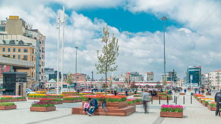 Taksim square timelapse, Istanbul, Turkey. Cars and people in the busy Taksim Square. Colorful tulip flowers on flowerbed. Cloudy sky at spring day Standard-Bild