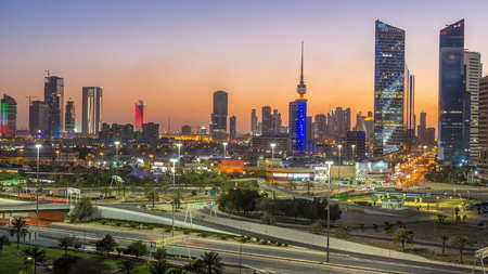 Skyline with Skyscrapers day to night transition timelapse in Kuwait City downtown illuminated at dusk. Kuwait City, Middle East. View from rooftop