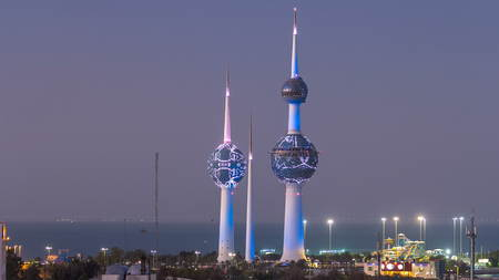 KUWAIT - CIRCA MARCH 2017: Top view of Kuwait Towers day to night transition timelapse illuminated at night - the best known landmark of Kuwait City. Kuwait, Middle East. View with palms and lunapark at foggy weather.