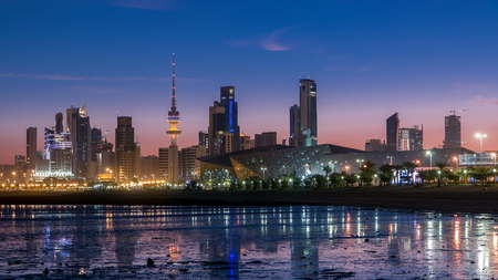 Seaside skyline of Kuwait city from night to day transition timelapse. Modern illuminated towers and skyscrapers reflected in water. Reklamní fotografie
