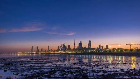 Seaside skyline of Kuwait city from night to day transition timelapse. Modern illuminated towers and skyscrapers reflected in water.