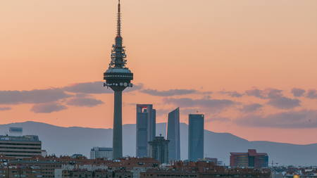 Madrid sunset skyline  timelapse with some emblematic buildings such as Kio Towers, part of the Cuatro Torres Business Area and the Piruli (TV Tower). 4K taken from the hills of Tio Pio Park, Vallecas-Neighborhood Banco de Imagens
