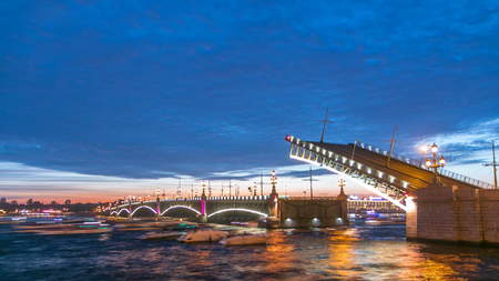 Opening Trinity bridge timelapse and pleasure boats are on Neva river in Saint-Petersburg, Russia. White nights period in city Stock Photo