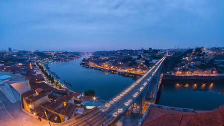 Day to Night transition view of the historic city of Porto, Portugal timelapse with the Dom Luiz bridge fisheye 4K Stock Photo