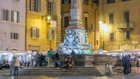 View of Rotonda square and Fountain timelapse near Pantheon at night light. Rome, Italy. People walking and sitting at fountain