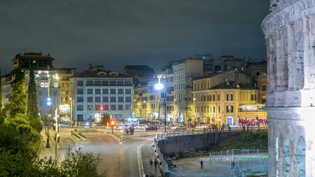view of square near Colosseum illuminated at night timelapse in Rome, Italy. Top view. Traffic on the road