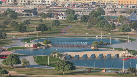 Bridge with fountain and lake in the Aspire park timelapse in Doha, Qatar. Aerial top view early morning during sunrise