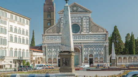 Basilica of Santa Maria Novella in the homonym square timelapse in Florence. Flowerbeds and green grass. People sitting on a bench. Blue sky at summer day
