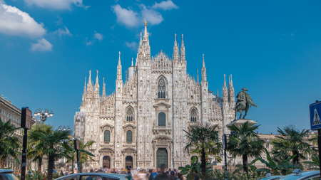 The Duomo cathedral timelapse with palms and monument. Front view with people walking on square. Blue cloudy sky at summer day. The Gothic cathedral took nearly six centuries to complete. It is the fifth largest cathedral in the world and the largest in italy Imagens