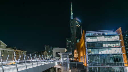 Milan Porta Nuova business district at night transition timelapse. Pedastrian bridge and Lights in windows of skyscrapers