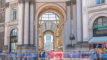 Entrance to the Galleria Vittorio Emanuele II from back side timelapse. This gallery is tourist attraction of Milan. Blue cloudy sky at summer day. People walking inside 報道画像