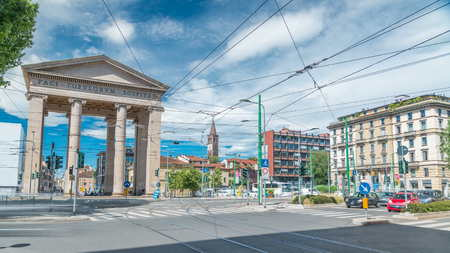 Street view on Ticinese city gate and tram timelapse with traffic in Milan. The gate of Porta Ticinese is one of the landmark buildings of Milan and a popular tourist attraction Stock Photo