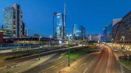 Milan skyline with modern skyscrapers in Porta Nuova business district day to night transition timelapse in Milan, Italy, after sunset. Traffic on the road. Light in windows. Top view from bridge Stock Photo