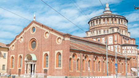 Santa Maria delle Grazie timelapse with blue cloudy sky. Milan, Italy. People walking around. Traffic on the road. This church and the adjacent Dominican convent were built during the 15th century.