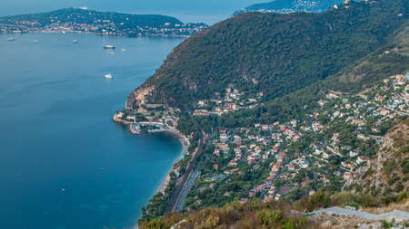 Morning timelapse view of the Mediterranean coastline with boats and medieval houses from the top of the town of Eze village on the French Riviera after sunrise.
