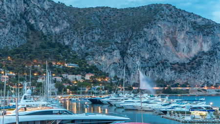 Port and landscape timelapse of Beaulieu sur mer after sunset, France. Boats and yachts on foreground. Mountains on background.