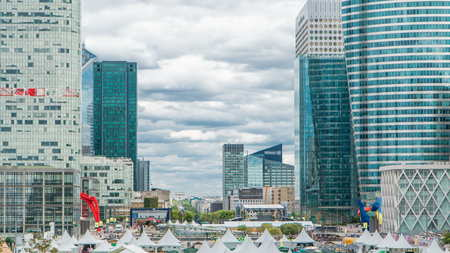Unique skyscraper timelapse in famous financial and business district of Paris - La Defense. Cloudy sky at summer day. Arc de triomphe visible on the horizon.