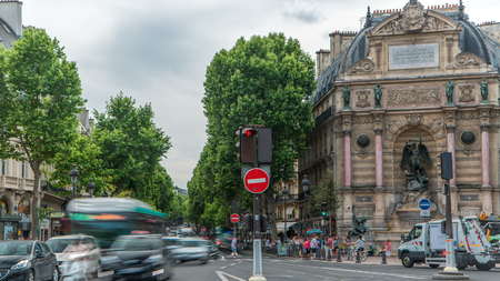 Street view of Place Saint-Michel with ancient fountain timelapse, Paris. Traffic on the road with cars and people. Cloudy sky at summer day