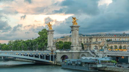 Bridge of Alexandre III spanning the river Seine timelapse. Decorated with ornate Art Nouveau lamps and sculptures. View from Invalides bridge. Paris. France. Blue cloudy sky before sunset