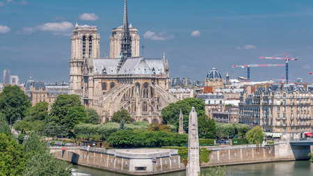Paris Panorama with Cite Island and Cathedral Notre Dame de Paris on the background timelapse from the Arab World Institute observation deck. Top view. Green trees, Seine river, Blue cloudy sky at summer day. France. Foto de archivo