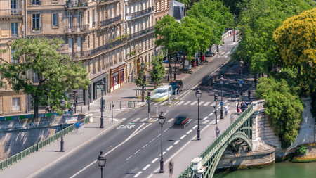 Panorama of Paris timelapse with traffic on Bridge of Sully. View from observation deck of Arab World Institute (Institut du Monde Arabe) building. Top aerial view. Green trees, Seine river, Blue cloudy sky at summer day. France.