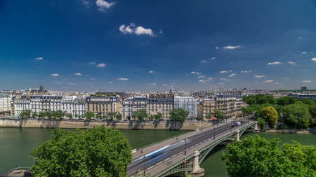 Panorama of Paris timelapse with houses and traffic on Bridge of Sully. View from observation deck of Arab World Institute (Institut du Monde Arabe) building. Top aerial view. Green trees, Seine river, Blue cloudy sky at summer day. France.