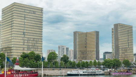 View of the National Library of France timelapse, whose four buildings in the form of open books surround a wooded area. View from Bridge of Tolbiac with reflection on Seine river. Paris, France