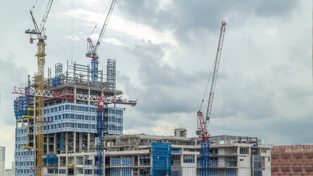 Construction site of a modern skyscraper in Singapore timelapse. Aerial view from above. Clouds on background