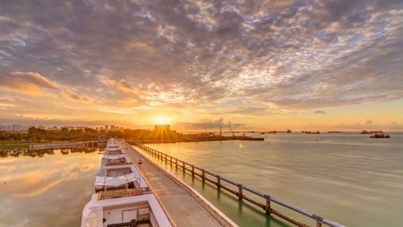 Beautiful sunrise scene at Marina Barrage timelapse. Orange sky and clouds with sun beams. It is Singapore's 15th reservoir and the first in the heart of the city.