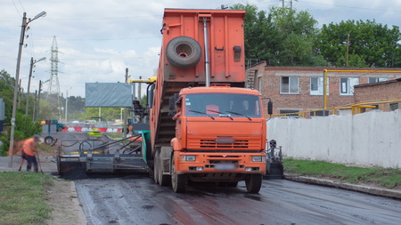 A paver finisher, asphalt finisher or paving machine placing a layer of asphalt during a repaving construction project timelapse. Trucks with asphalt