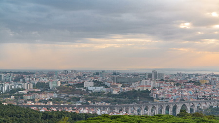 Panoramic view during sunrise over Lisbon and Almada from a viewpoint in Monsanto morning . Aerial top view with golden light, colorful clouds and rays of light. Aqueduct of the Free Waters and roofs