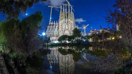 BARCELONA, SPAIN - CIRCA OCTOBER 2018: Sagrada Familia, a large Roman Catholic church in Barcelona, Spain day to night transition . Spires and cranes. Reflections on water of lake