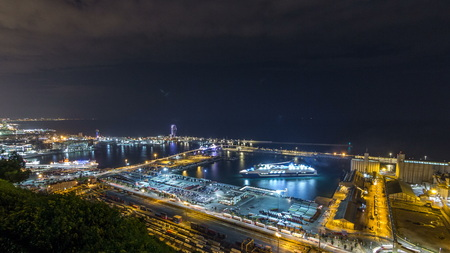 Night skyline from Montjuic with Port Vell , Barcelona, Catalonia, Spain. Aerial top view from hill with ship and terminal 免版税图像