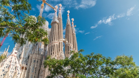 BARCELONA, SPAIN - CIRCA OCTOBER 2018: Top of Sagrada Familia, a large Roman Catholic church in Barcelona, Spain . Spires and cranes. Green trees, blue cloudy sky at autumn day