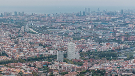 Barcelona and Badalona skyline with roofs of houses, river and sea on the horizon at evening . Aerial view from Iberic Puig Castellar Village viewpoint on top of hill