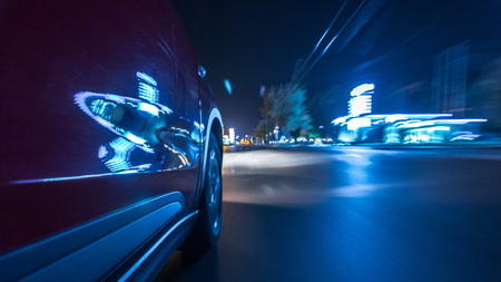 Driving from Side of Car moving on a night highway  , road with lights reflected on car on high speed. Rapid rhythm of a modern city.