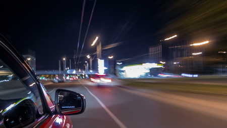 Driving from side of fast car moving on a night avenue in city  , road with lights reflected on car on high speed. Rapid rhythm of a modern city.