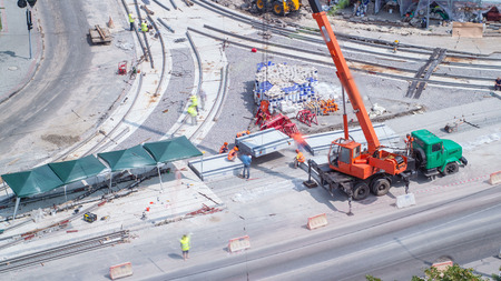 Unloading and installing concrete plates from truck by crane at road construction site timelapse. Industrial workers with hardhats and uniform. Aerial top view. Reconstruction of tram tracks on intersection Stockfoto